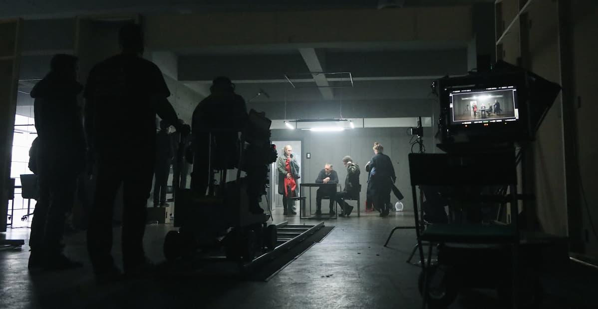 Laajassa kuvassa työryhmää kuvaamassa kellarimaisessa huoneessa Sorjosen kohtausta. Kameran ajoradan päässä päänäyttelijät esittämässä kuulustelutilannetta.