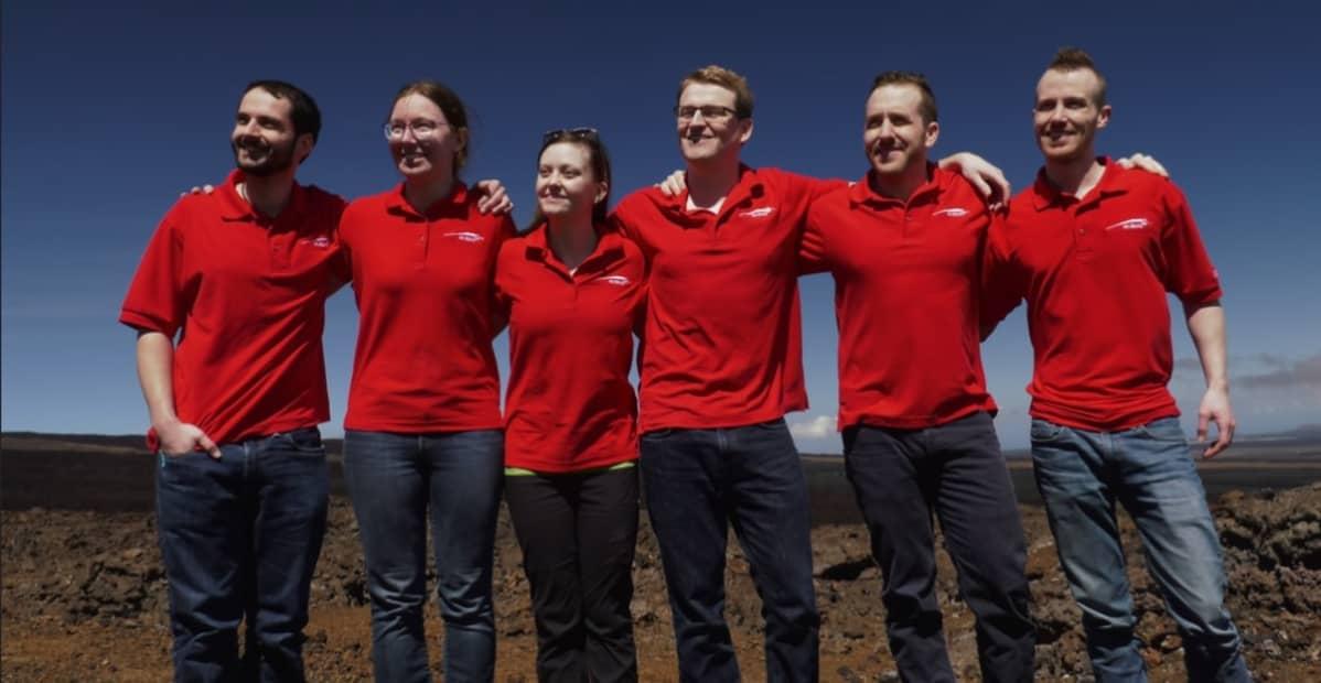 Neljä miestä ja kaksi naista punaisissa T-paidoissa, kädet toistensa hartioilla.