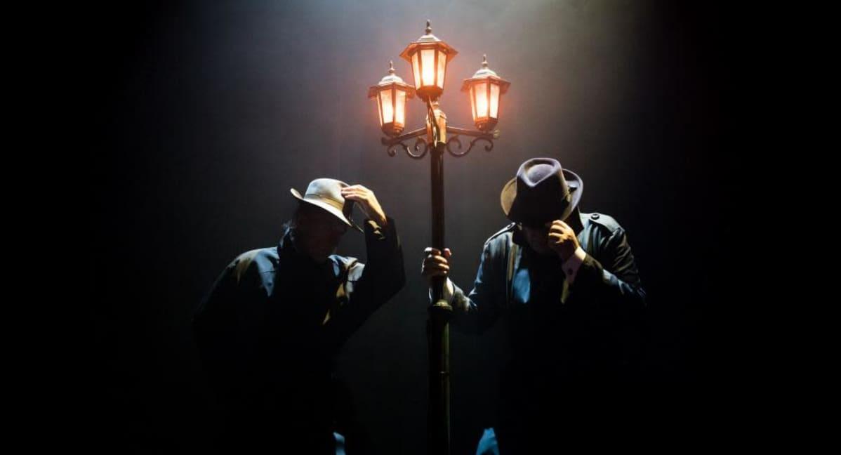Kaksi hattupäistä miestä katulyhdyn alla lähes pimeässä.