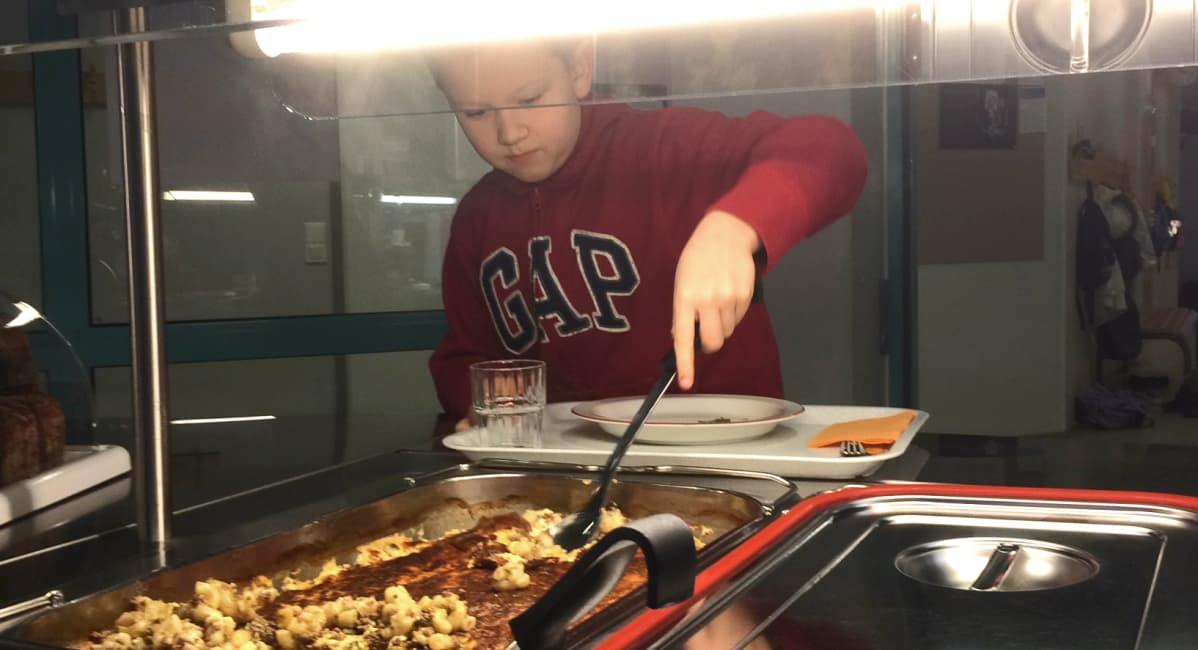 poika ottaa ruokaa kauhalla koulussa