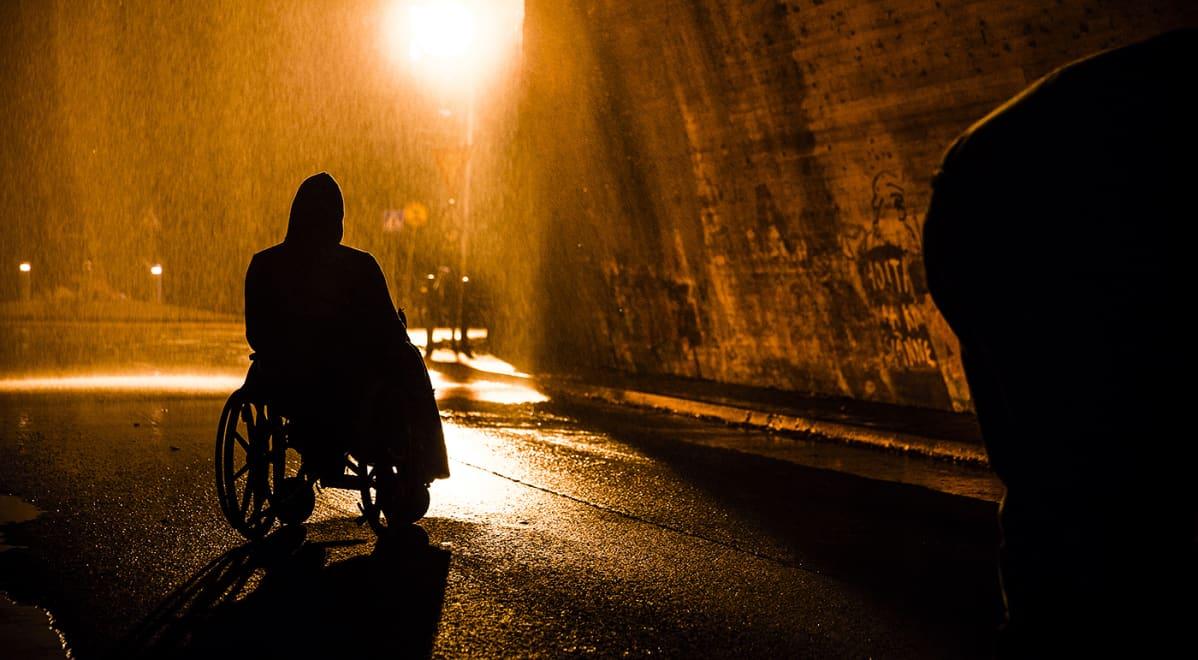 Pyörätuolissa istuvan miehen siluetti tihkusateisessa yössä, otos elokuvasta Rendel