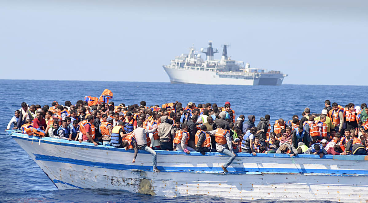 Etualalla merellä on suuri joukko ihmisiä veneessä. Kauempana näkyy suuri alus.