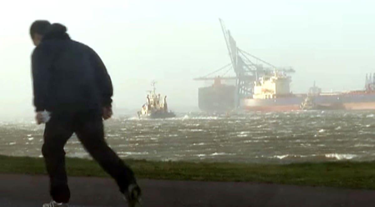 mies kävelee rannalla myrskyssä