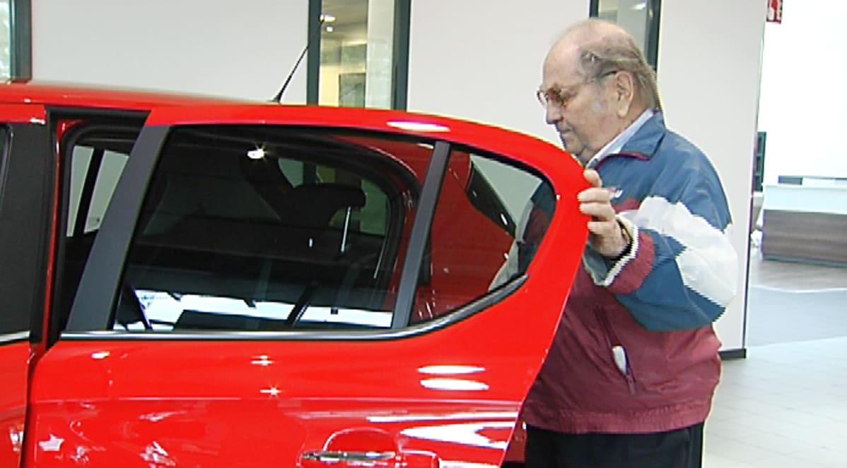 mies tutkii autoa