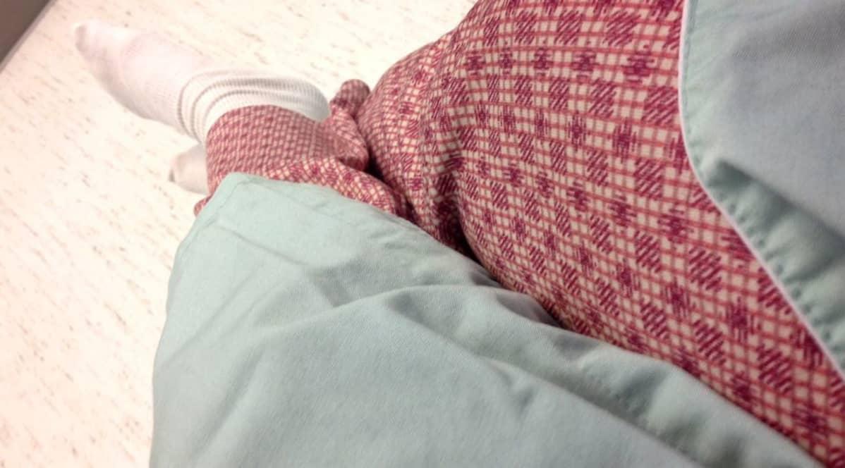 Potilas istuu sairaalasängyllä leikkausvaatteet päällään.