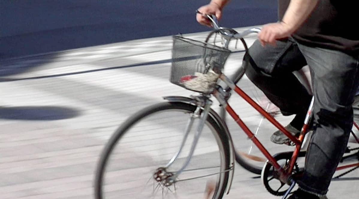 Anonyymi henkilö ajaa polkupyörällä.