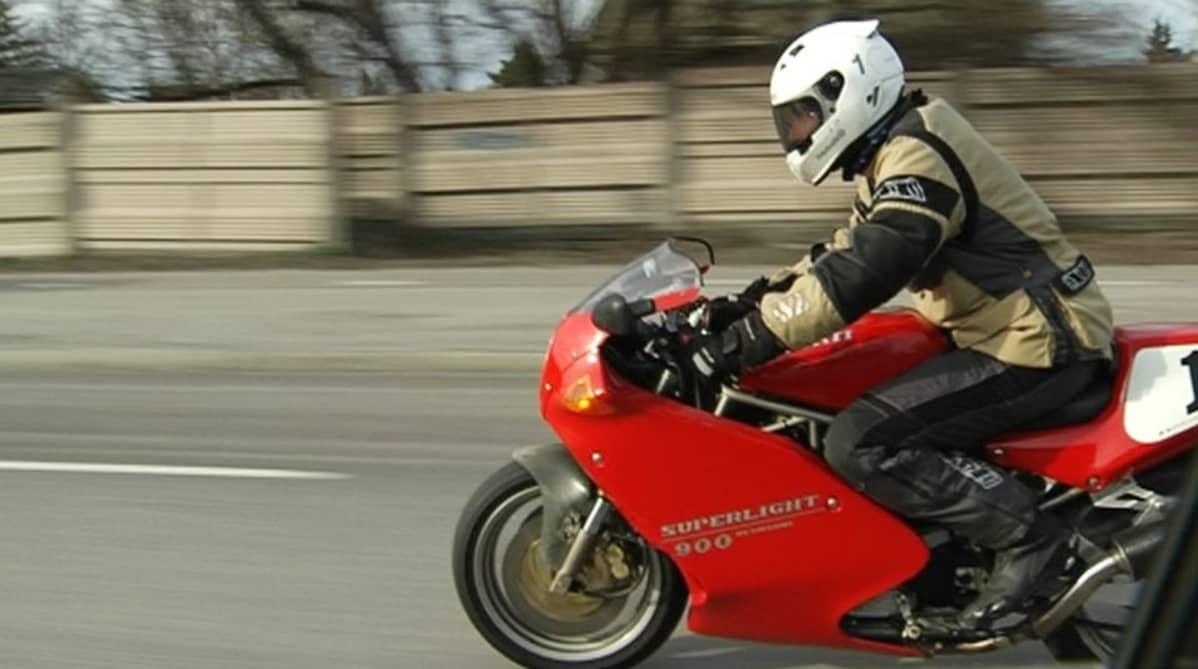 Moottoripyörä liikkeessä auton ikkunasta kuvattuna.
