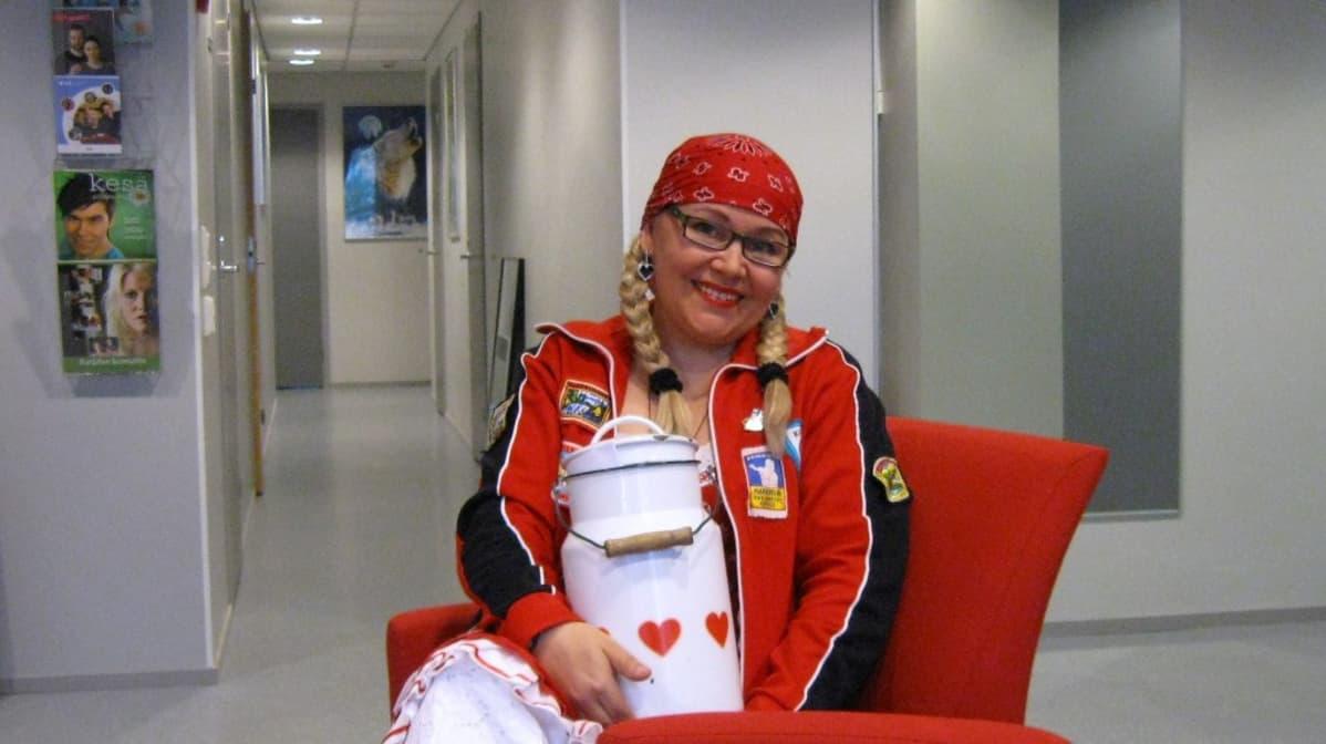 Punaisiin pukeutunut Kirsi Korhonen maitotonkka sylissään.