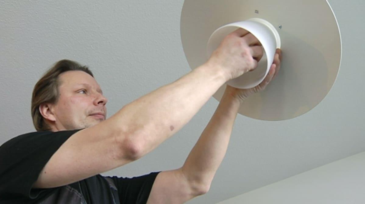Sähköurakoitsija Timo Hyytiälä vaihta lamppua.