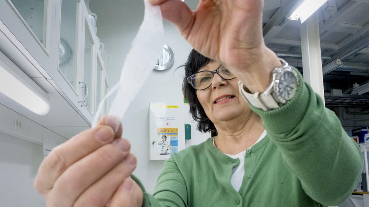 Nainen pitelee kädessään muovisuikaletta.