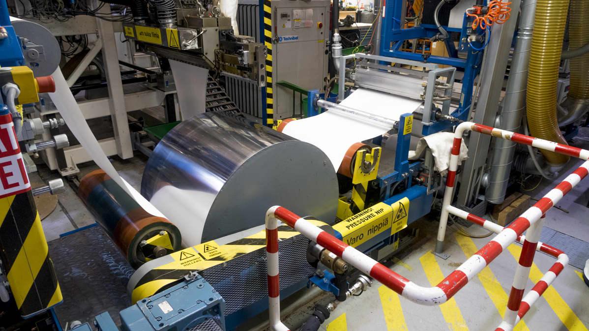 Paperi kulkee koneella telalta toiselle.