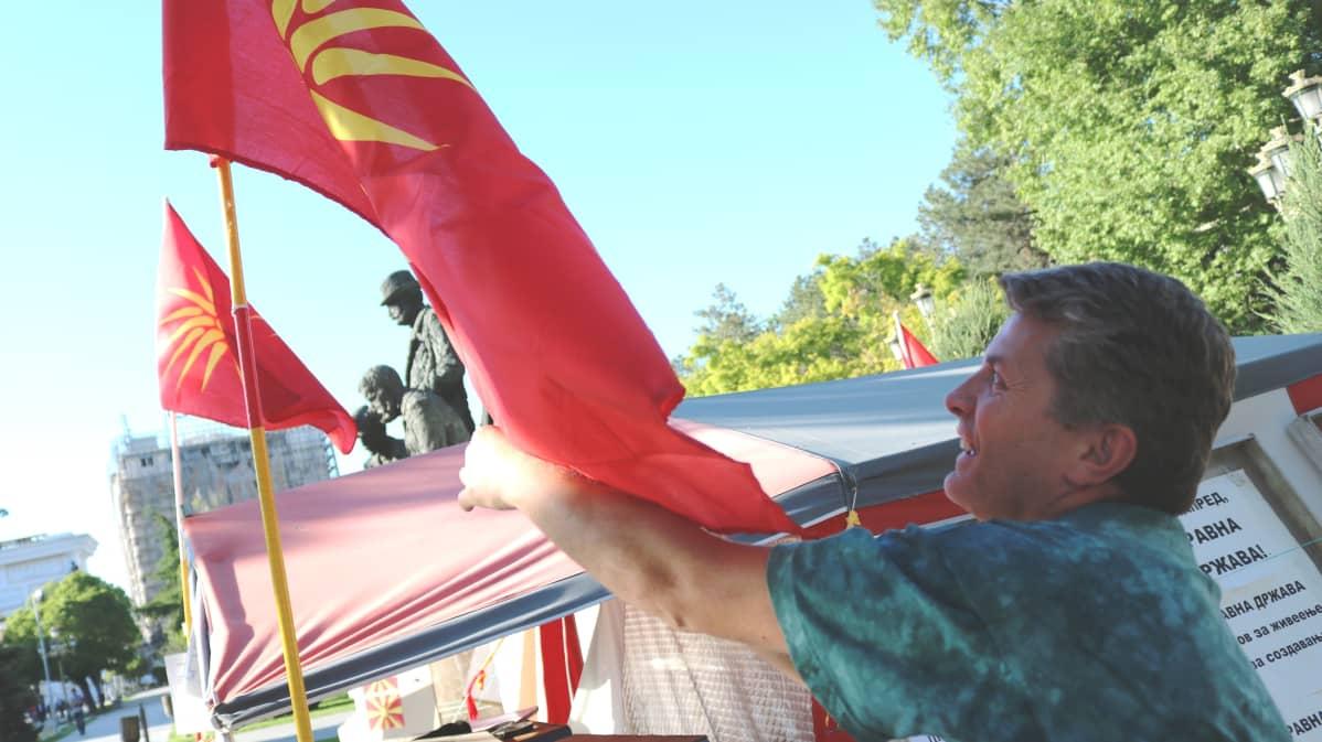 Goce Andjelkovski vastustaa Makedonian nimen muuttamista. Mielenosoitusleirissä liehuu Makedonian vanha lippu, jonka käytöstä luovuttiin 1990-luvulla koska se muistuttaa Kreikan puoleisen Makedonian maakunnan lippua.