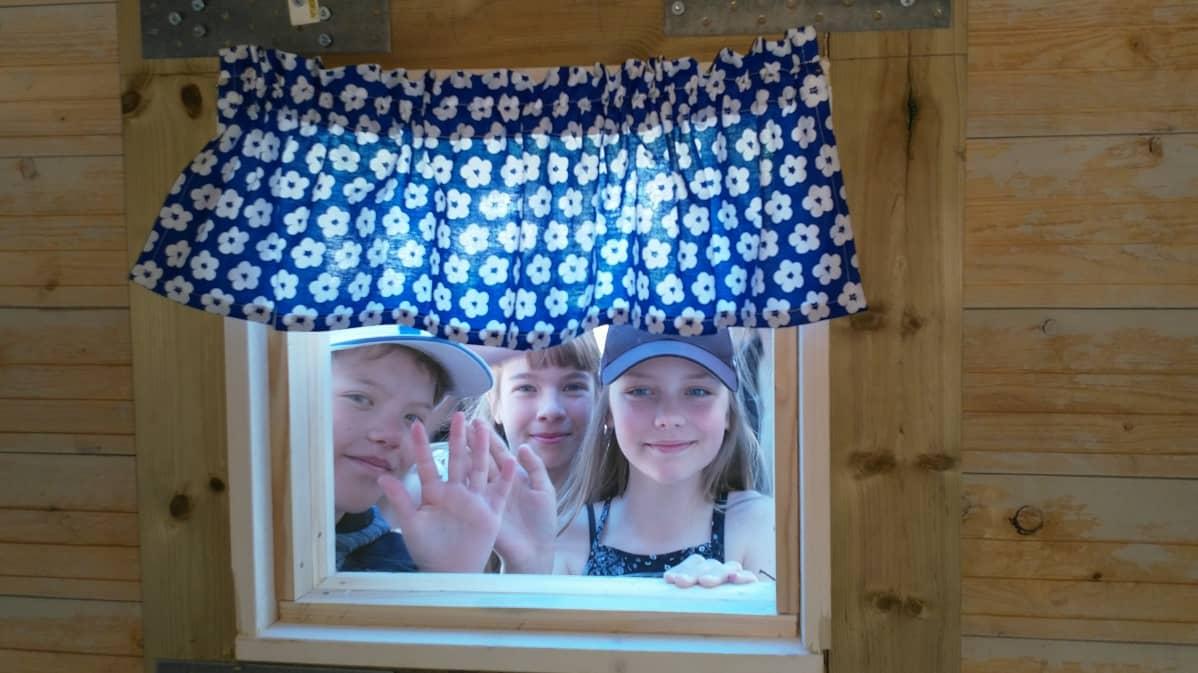 Kuvassa kolme lasta vilkuttaa leikkimökin ikkunasta