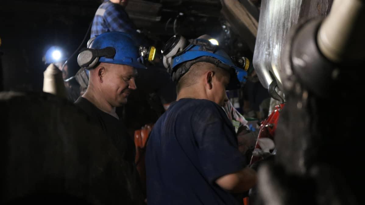 Bogdankan kaivosmiehet valmistelevat käyttökuntoon konetta, joka repii hiilen esiintymän seinästä.