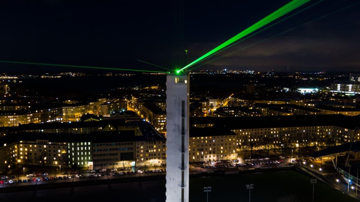 """Stadionin torni pimeää taivasta vasten, vihreitä lasersäteitä ja kaupungin valoja. Valoshow sykkii läpi yön, ja morsettavat taivaalle merkkisarjaa: """"2020–2021""""."""