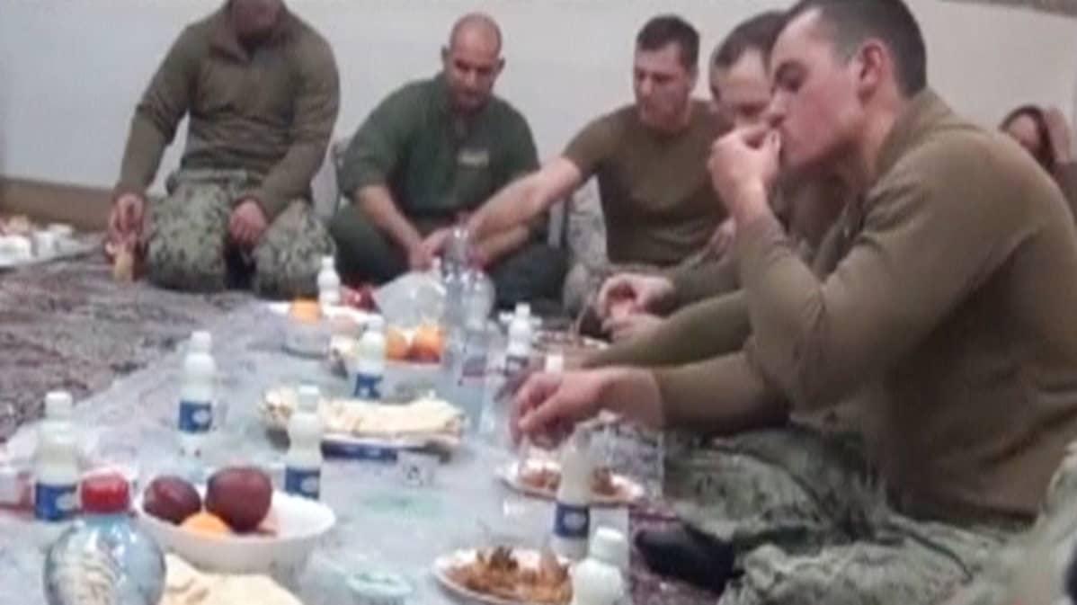 Yhdysvaltain merivoimien vangitut sotilaat syövät lattialla.