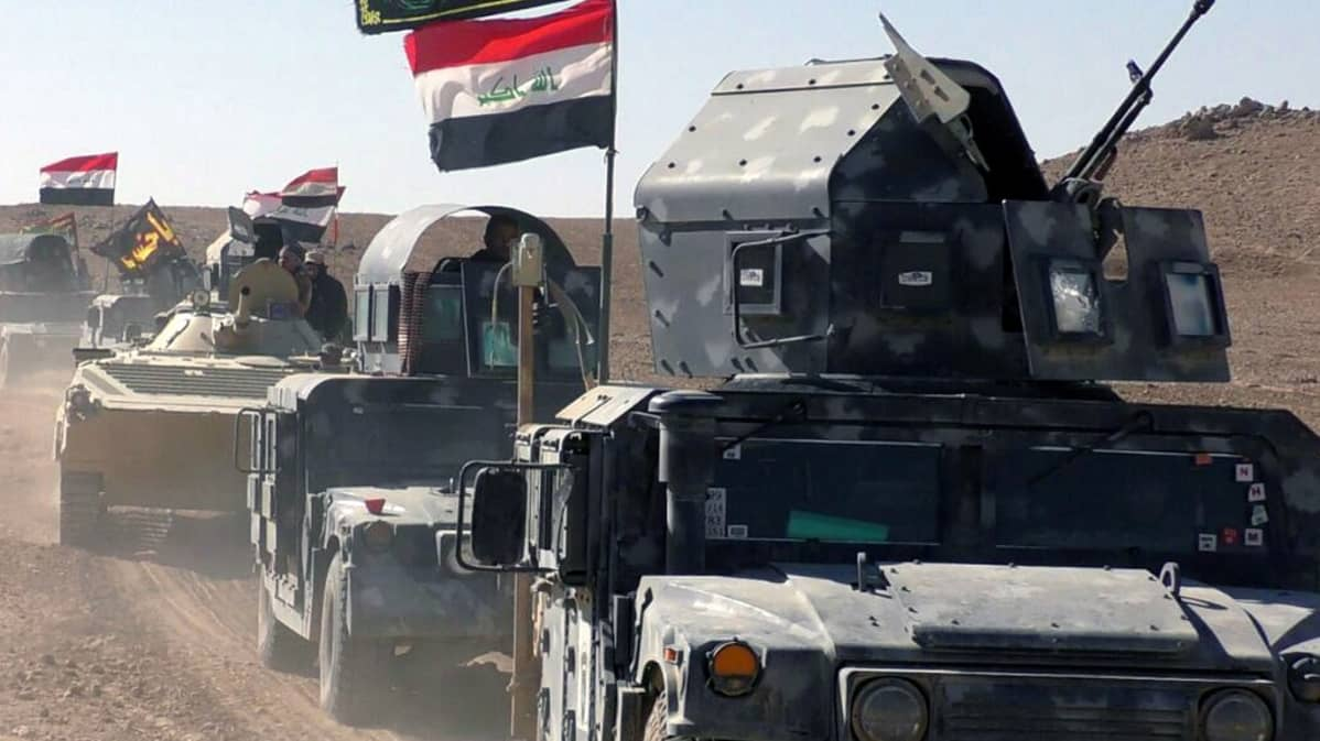 Panssaroituja ajoneuvoja pölyisellä tiellä. Ajoneuvojen tangoissa liehuvat Irakin liput.