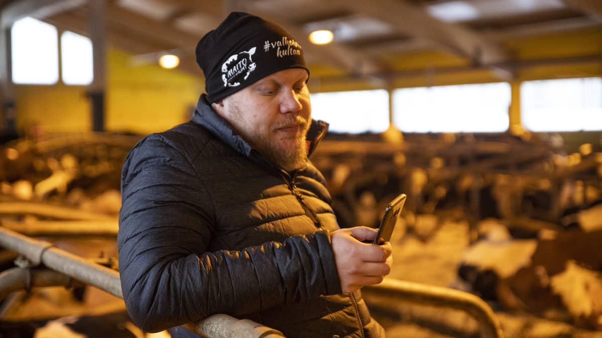 Mustolan isäntä Markus Heikkinen selaa puhelinta.