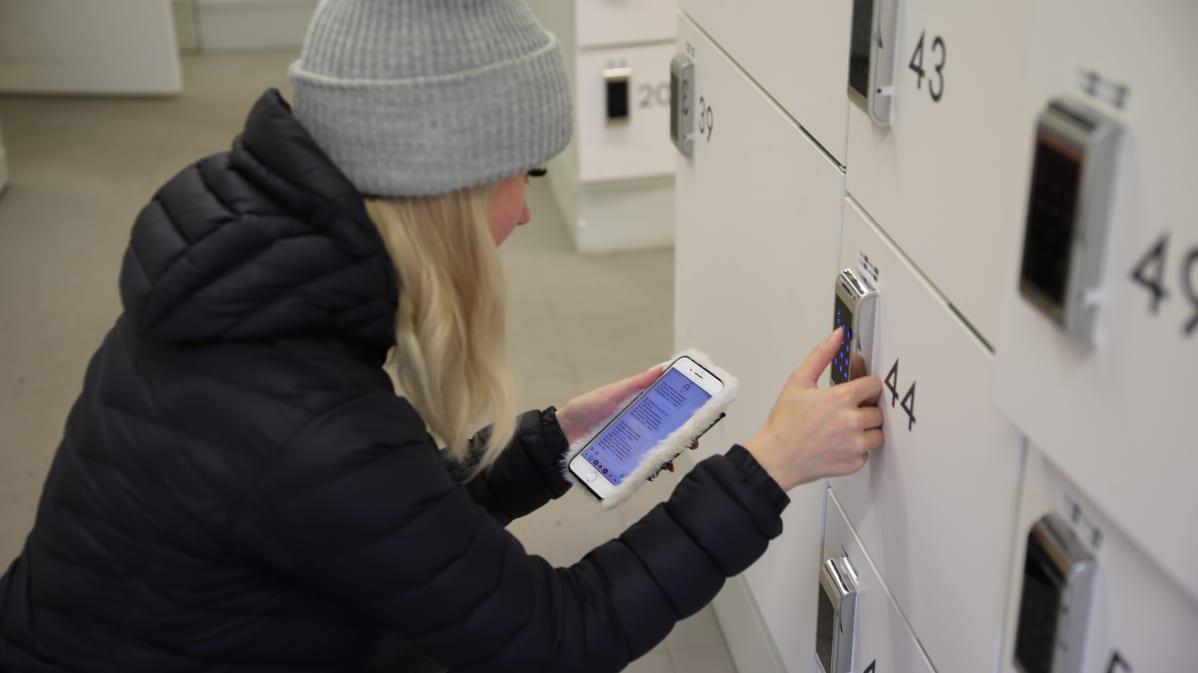 Nainen hakee ostoksiaan pakettiautomaatista