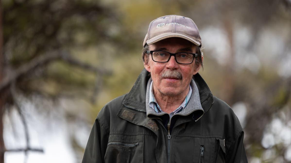 Vihreätakkinen, harmaaviiksinen Esko Aikio lippalakissa ja silmälasit päässä katsoo kameraan.
