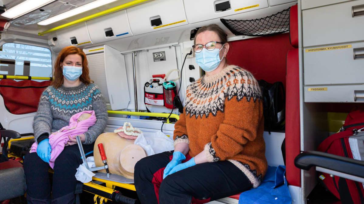 Kätilöt Hanna-Mari Huttunen ja Lea Hiltunen. Kuvassa on nukkeja sekä äiti ja vauva.