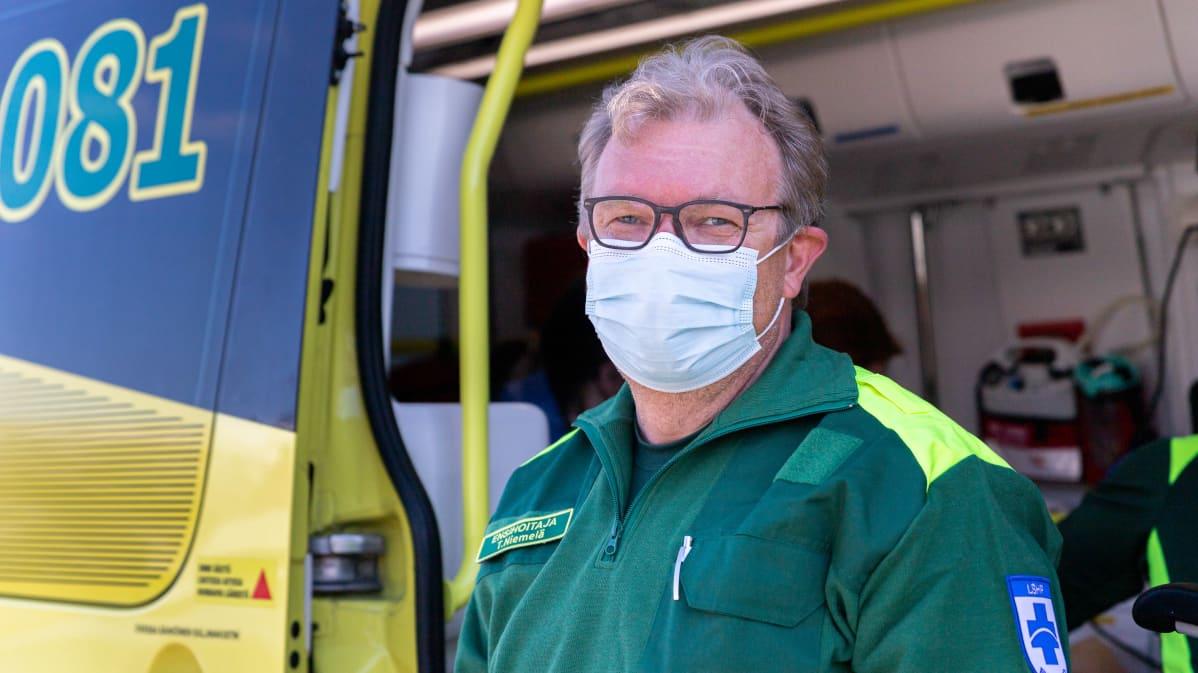 Utsjoen ensihoitaja Tapio Niemelä katsoo kameraan ambulanssin edessä.