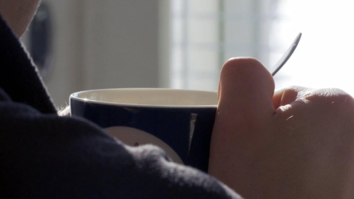 Mies istuu kahvikuppi kädessä