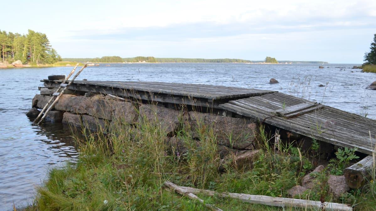 Kivinen laituri meren rannassa.
