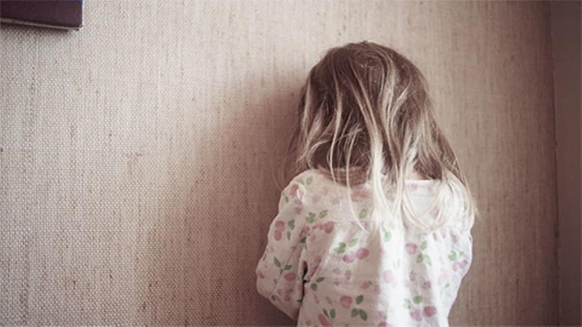 Pikkutyttö kääntyneenä seinään vasten.