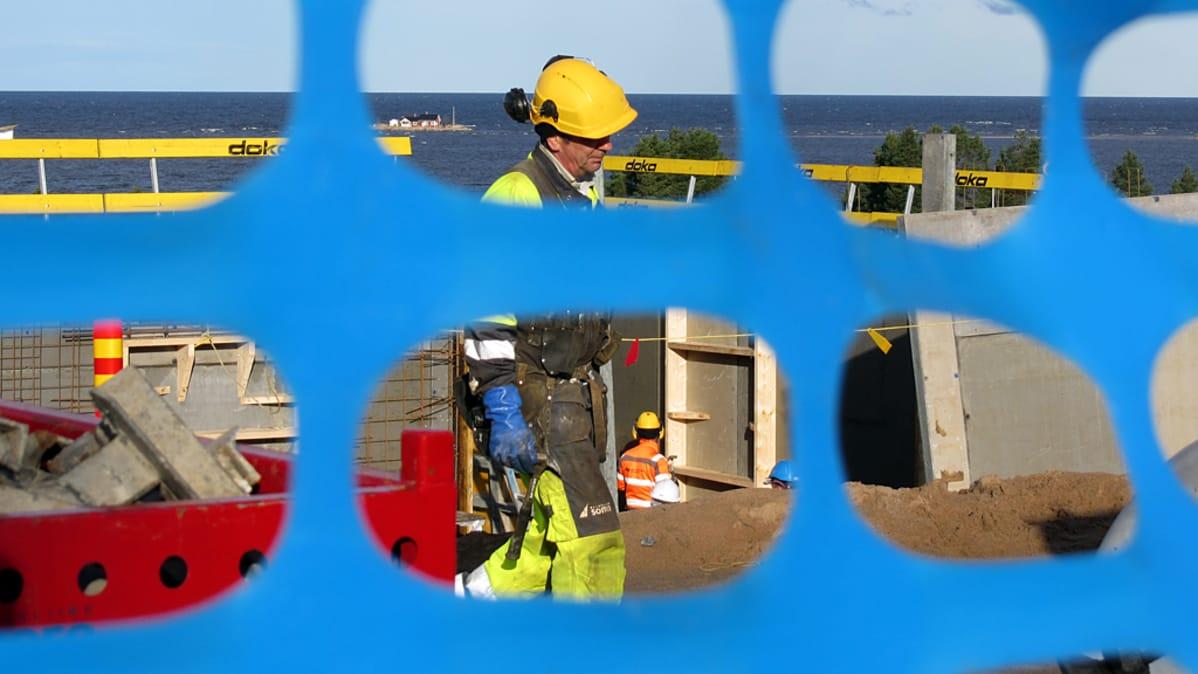 Rakennusmies kuvattuna sinisen, muovisen verkkoaidan läpi. Taustalla meri.