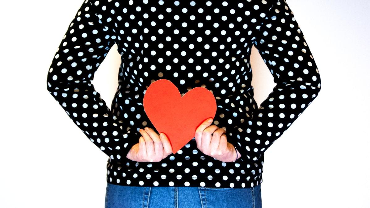Nainen pitelee sydäntä selkänsä takana.