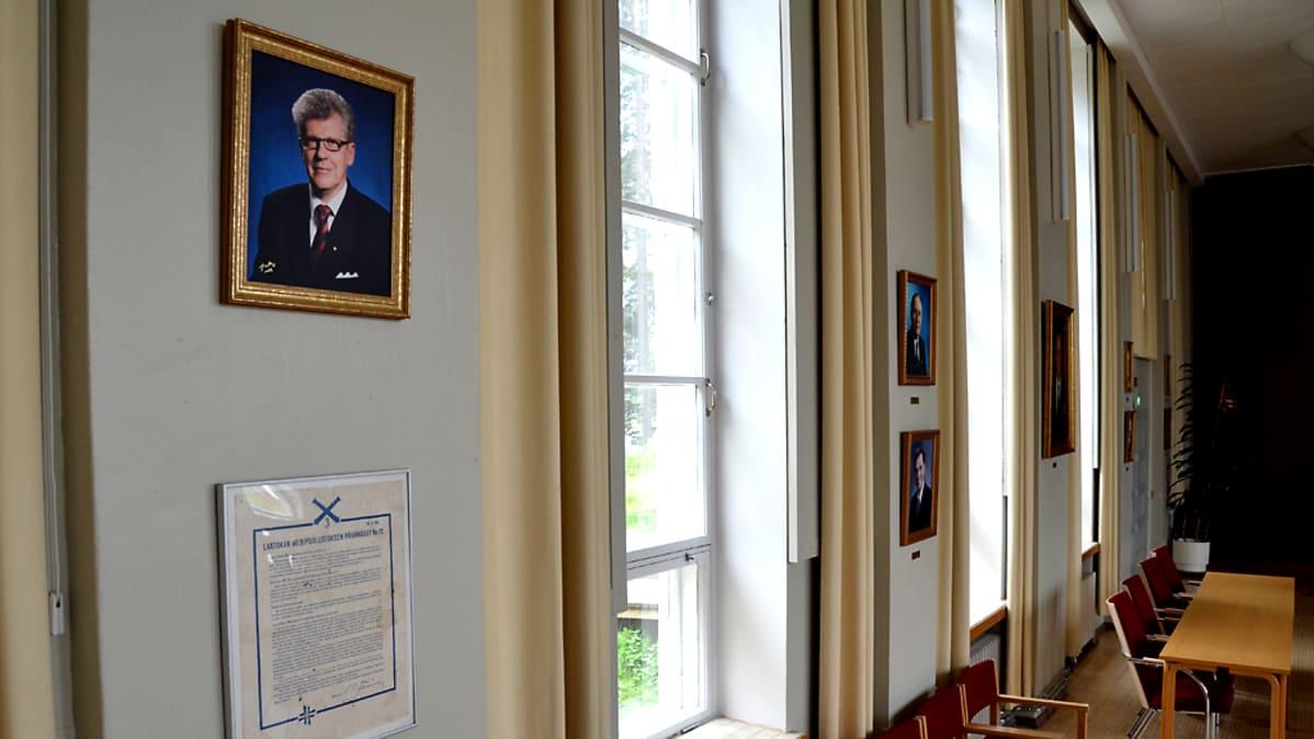 Kunnanjohtien kuvia valtuustosalin seinällä.