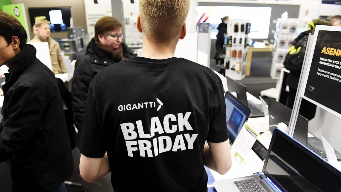 Kodinelektroniikkaketju Gigantin työntekijällä on päällään paita jossa  mainostetaan Black Fridayta. c210c5e927