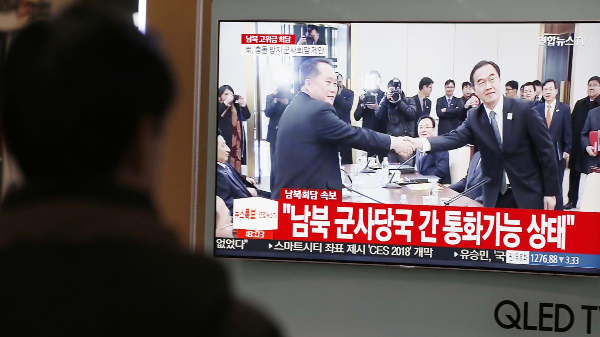 Mies katsoo televisiota eteläkorealaisella juna-asemalla.