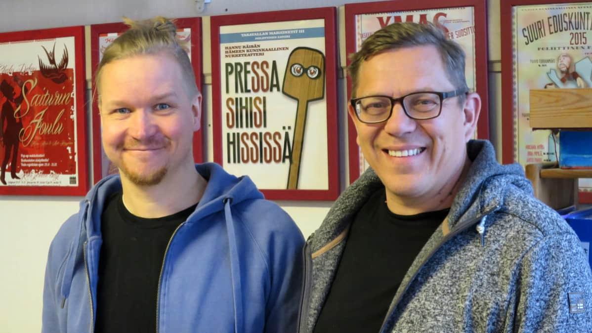 Kaksi miestä hymyilee julisteiden edessä