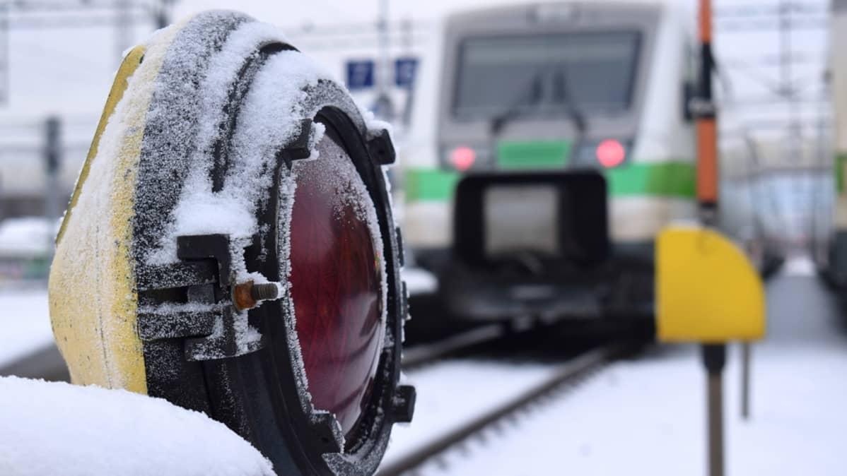 Punainen varoitusvalo ja Pendolino-juna Turun rautatieasemalla.