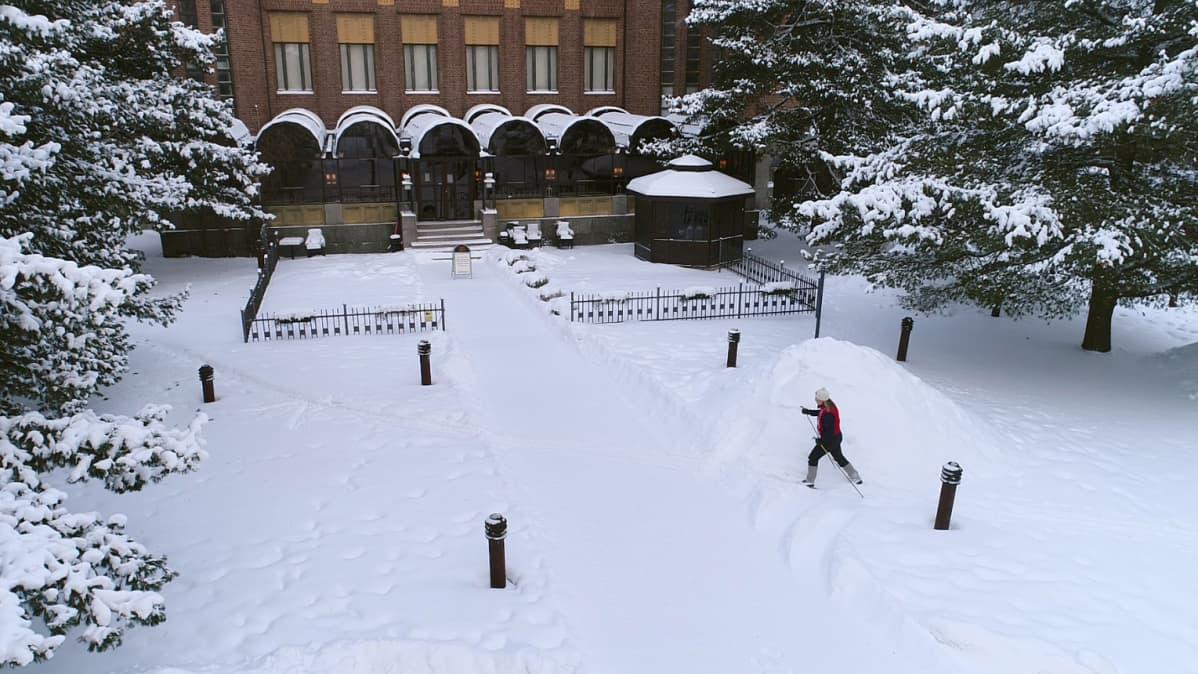 Hiihtäjä Joensuun kaupungintalon pihapuistossa.