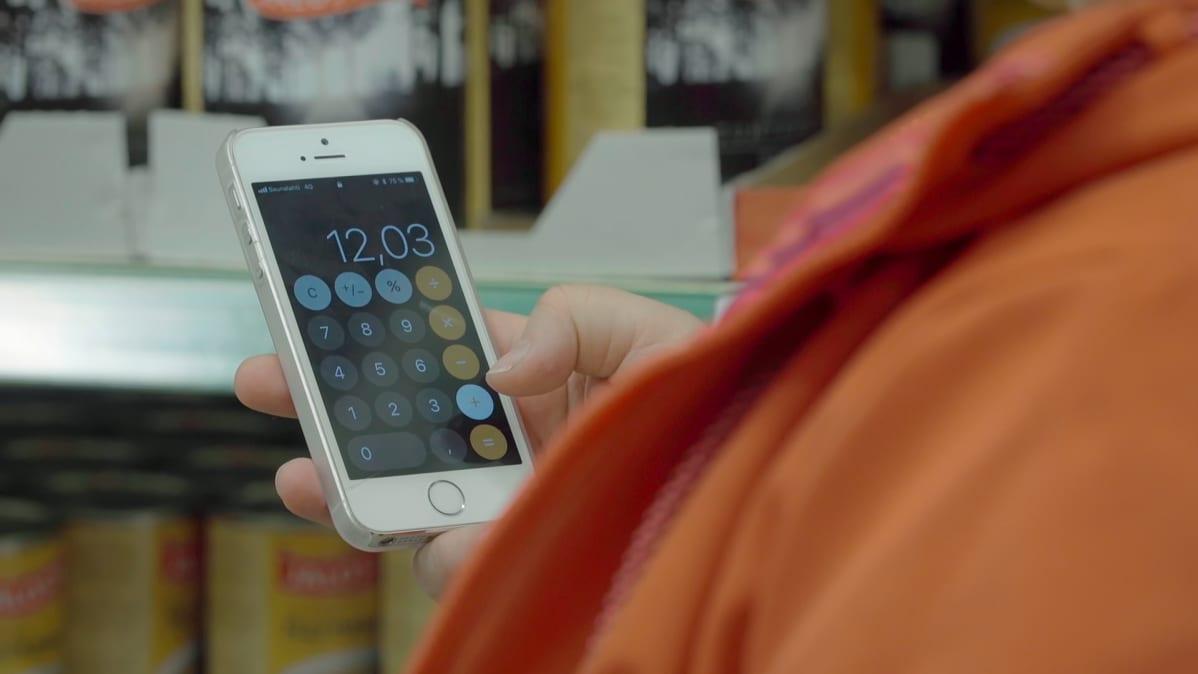 Tinna Pehkonen laskee puhelimen laskimella, riittävätkö rahat ostoksiin.