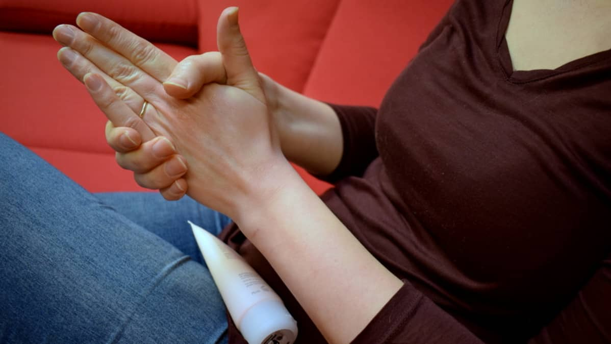 Nainen hieroo voidetta käsiinsä.