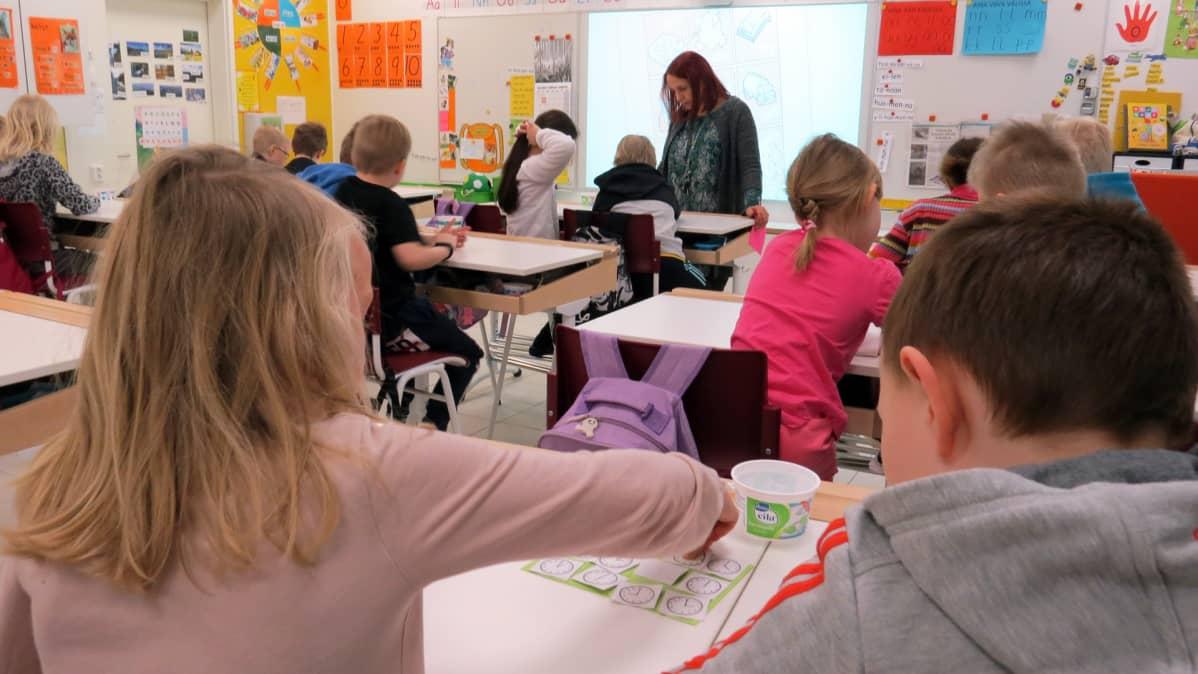 Koululaiset opettelevat kellotaulua oppitunnilla.