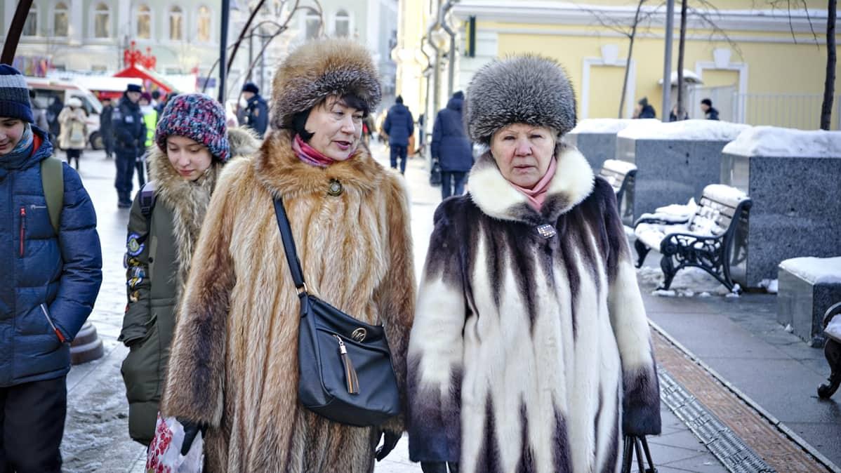 Kaksi naista kävelee kadulla turkiksissaan.
