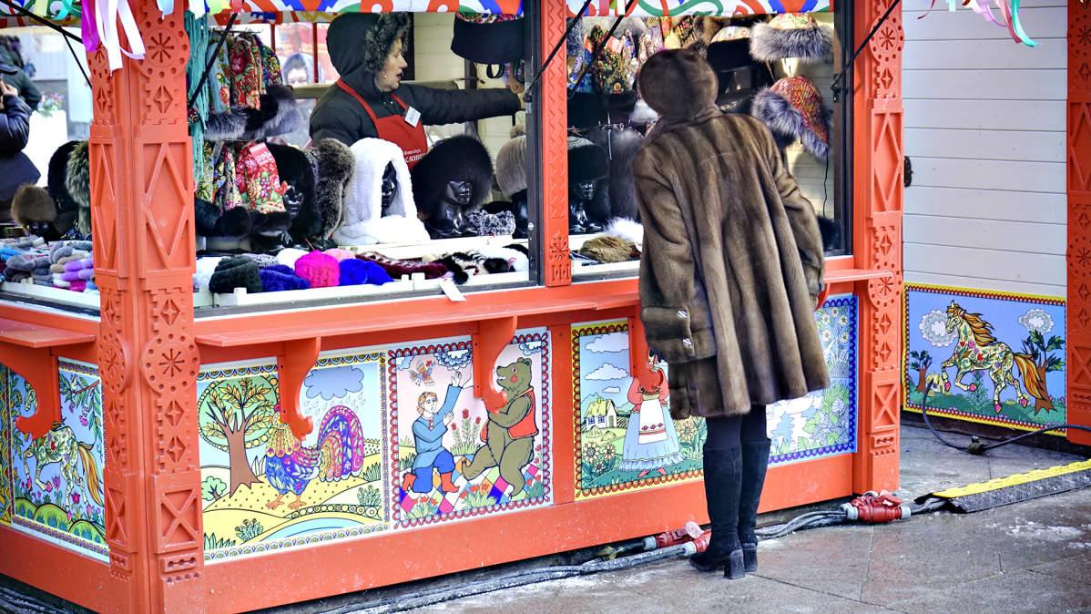 Nainen katselee kioskissa myytäviä karvahattuja.
