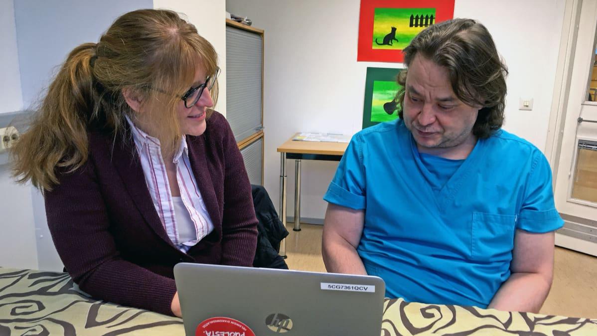 Työvalmentaja Jenni Oliveira ja Olli Honkila tietokoneen ääressä