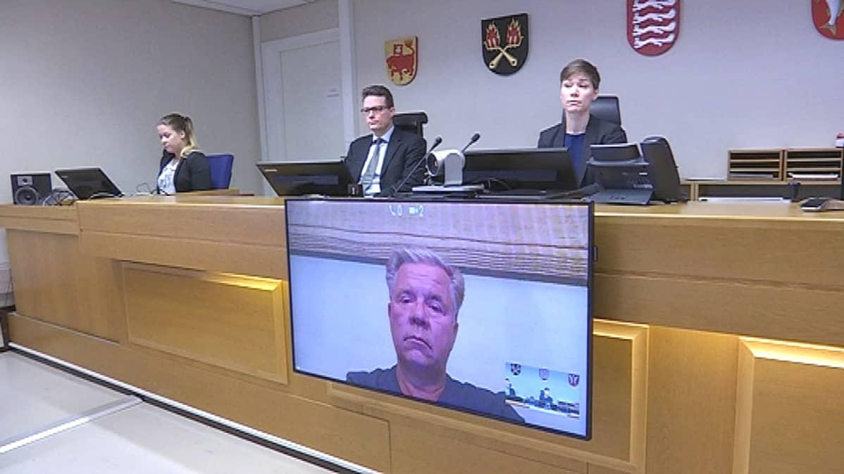 Kuva oikeussalista, jossa tuomarit kuuntelevat vastaajaa videoyhteyden kautta