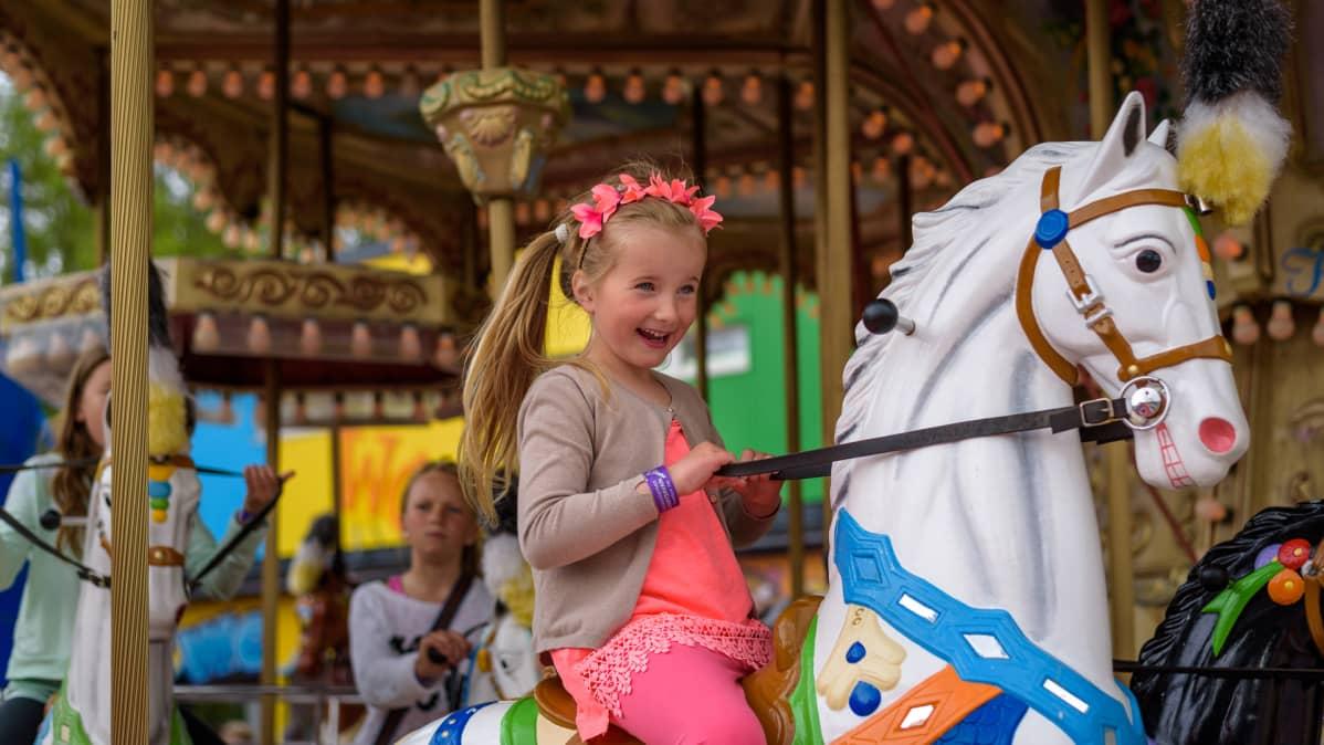 Lapsi matkustaa karusellissa hevosella