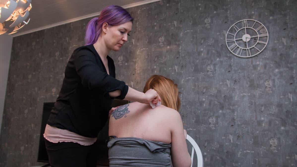 Doula sivelee raskaana olevan naisen hartioita hierontakivellä.
