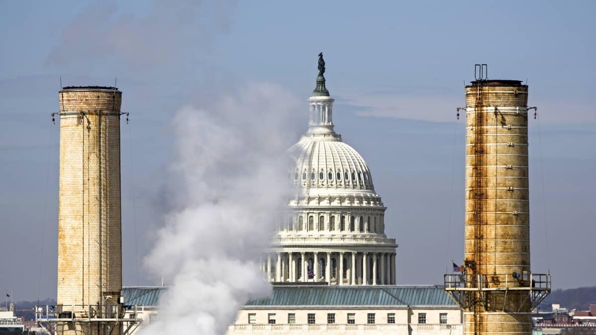 Yhdysvaltain kongressin rakennuksen kupoli näkyy kahden savupiipun välistä.