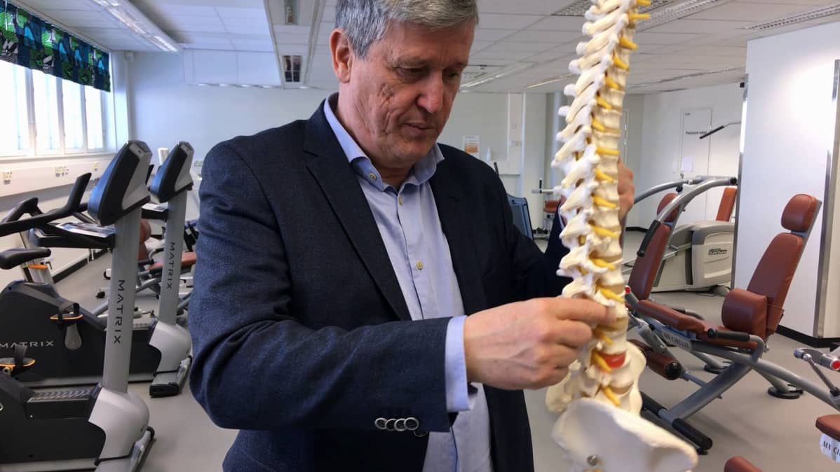 Professori Jaro Karppisen kädessä on malli selkärangasta