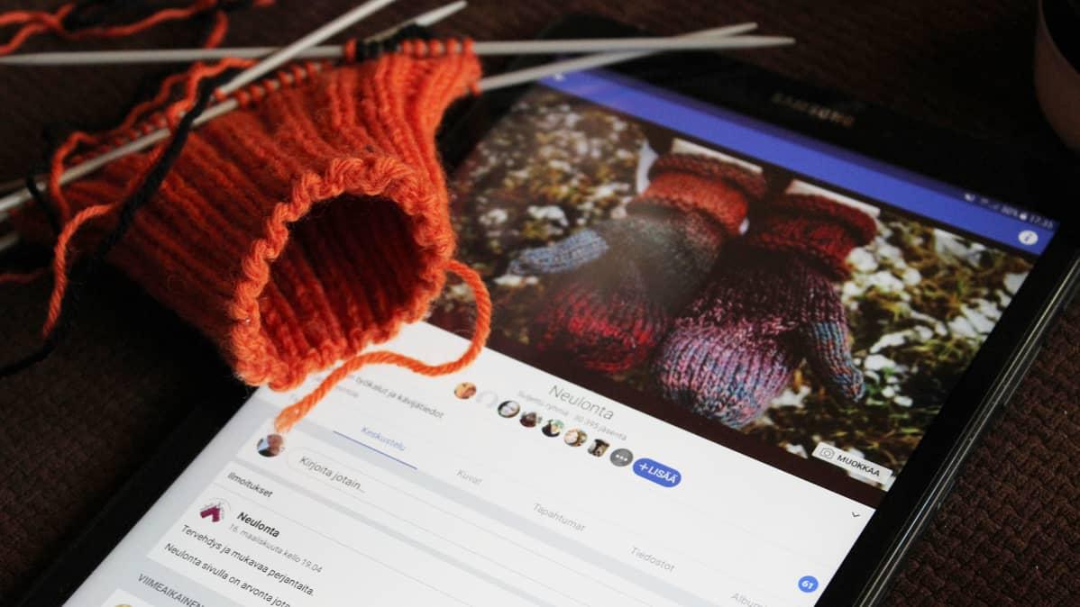 Tabletilla facebook auki, vieressä keskeneräinen käsityö