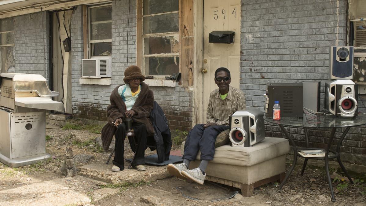 Nainen ja mies kuuntelevat musiikkia talon edessä.